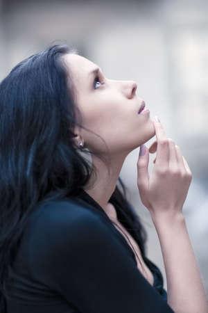 femme regarde en haut: Jeune femme pensive regardant portrait. DDL peu profond.  Banque d'images