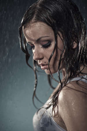 dark side: Young woman under the rain. Water studio photo. Stock Photo