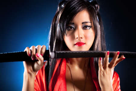 traditional weapon: Young japanese woman with samurai sword fashion. Focus on face. Stock Photo