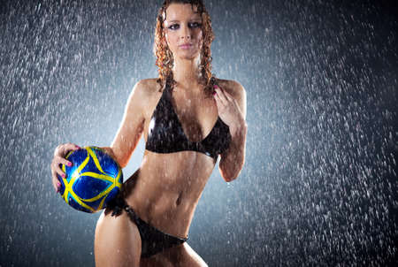 Young sexy woman football player. Water studio  photo