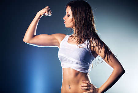 Young strong sexy woman showing her muscles. Stock Photo - 6903085