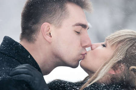 Young kissing couple outdoors winter portrait. photo
