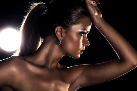 dark side: Young woman studio fashion portrait. Dark golden colors. Stock Photo