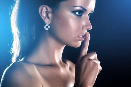 handsign: Young woman showing quiet handsign. On dark background.