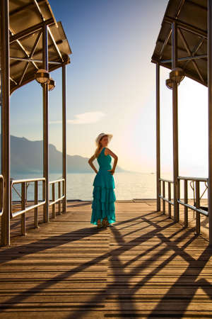 Young woman in blue dress standing at the moorage. photo