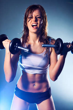 Young strong sexy woman with dumbbells. photo