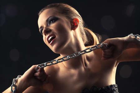 Young fashion woman breaking metallic chain. Stock Photo - 7096665