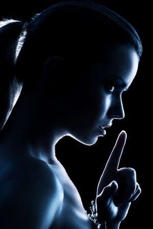 gesturing: Young woman showing quiet handsign. Dark blue silhouette.