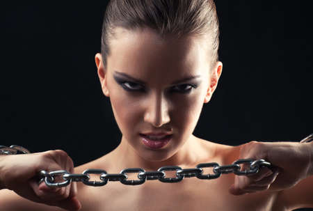 Young fashion woman breaking metallic chain. photo