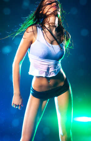 Young sexy dancing woman. Blue and green flashes on background. photo