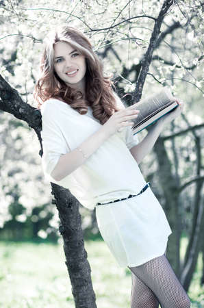 Young woman reading book in summer park. Bright white colors. photo
