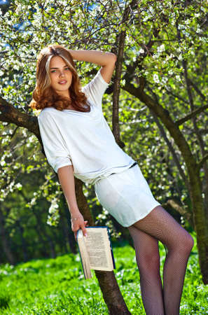 Young woman reading book in summer park. photo