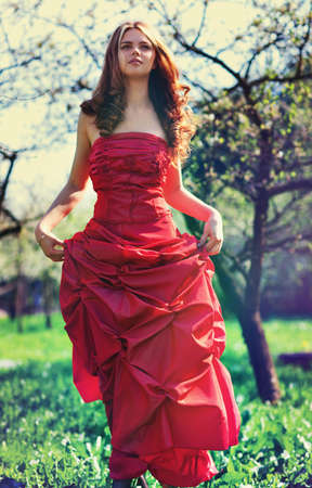 outdoor glamour: Young woman in red dress in garden. Film style colors.