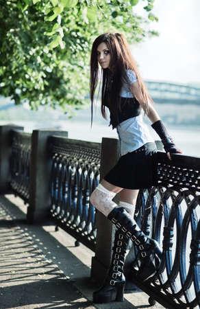 školačka: Young schoolgirl standing at the railing.