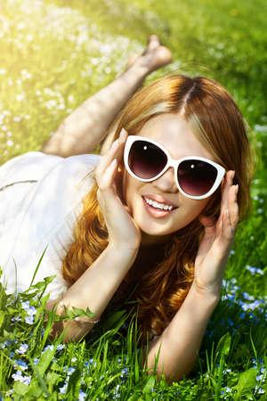 Young woman lying on grass fashion portrait. photo