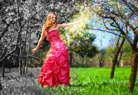 Young fairy woman in red dress painting garden. photo