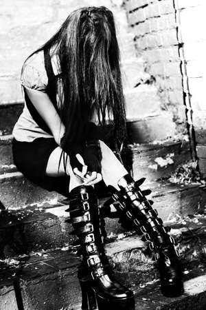 goth: Young goth woman sitting on stairs. Black and white colors. Stock Photo
