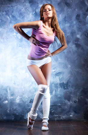 Young fitness woman. On gray wall background. photo