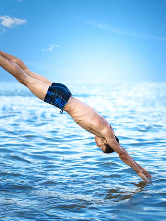 sky diving: Swimmer jumping to sea water. Stock Photo