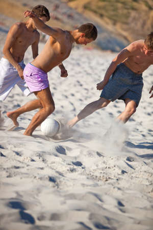 Young men playing soccer on beach. photo