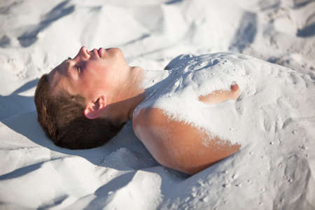 buried: Young man buried in sand.