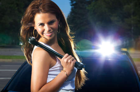 Young woman with screw key on car background. Bright flash effect. photo