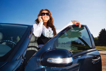 rich people: Young businesswoman talking on phone at her car. Stock Photo