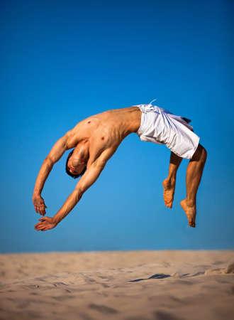 Joven saltando sobre la playa.