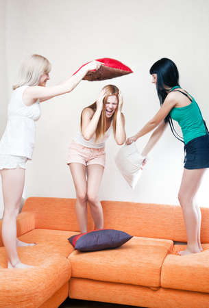 Young women fighting on pillows. Bright white colors. photo