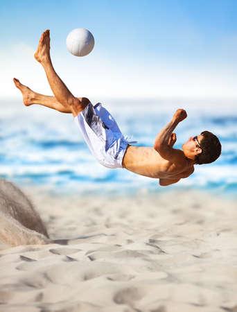 Młody mężczyzna gra Piłka nożna na plaży.