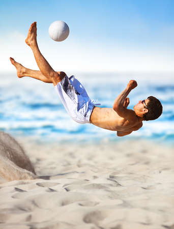 Young man playing soccer on beach. photo