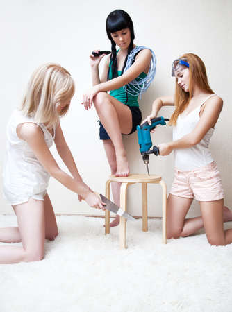 Young women repairing stool. Bright white colors. photo