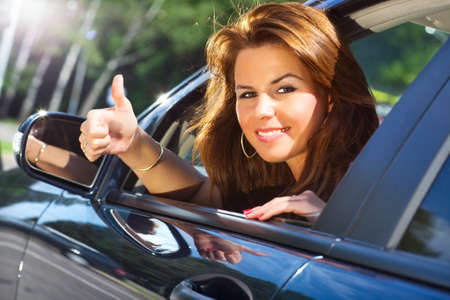 Young woman looking out of car and showing success handsign. Stock Photo