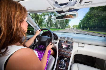 Young woman driving car. Wide angle interior view. Stock Photo - 7464636