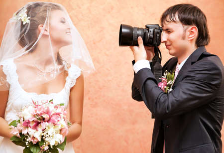 photographer: Husband taking picture of his wife on wedding. Stock Photo
