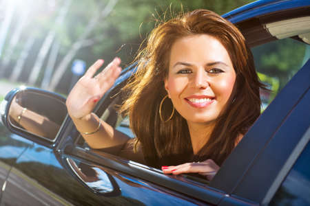 Young woman looking out of car and waving hand. photo