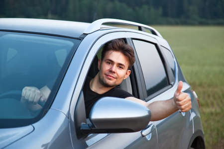 Young man looking out of car and showing success handsign.