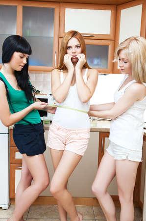 waist: Amigas medir la cintura en la cocina.