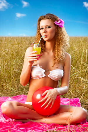 Young woman resting outdoors with cocktail. photo