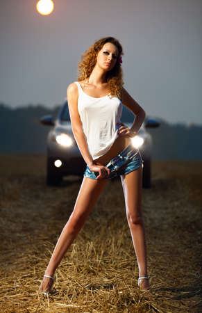 Young sexy woman in car headlights. photo