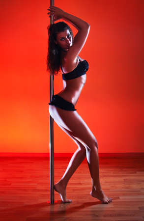Young sexy pole dance woman. Vibrant red light. photo
