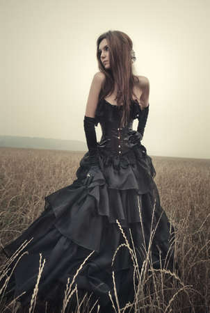gothic: Young goth woman walking on field.