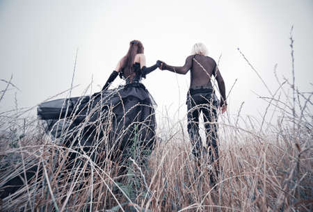 Young goth couple walking on field. Bright white colors. Stock Photo - 7677858