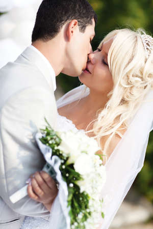 man woman kissing: Young wedding couple kissing. White colors. Stock Photo