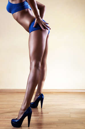 Young sexy woman legs. On wall background. photo