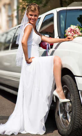 Young bride standing at the car. photo