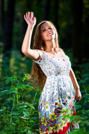 handsignal: Young woman in park waving hand.
