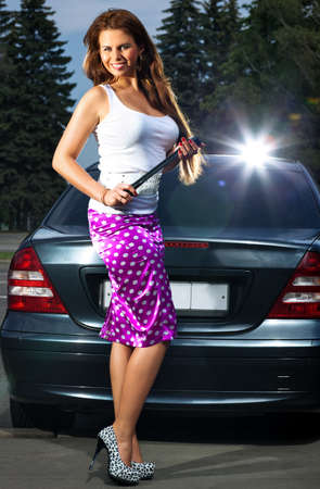 screw key: Young woman with screw key on car background. Bright flash effect.