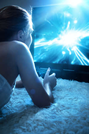 computer games: Young woman playing in computer games at night. Stock Photo
