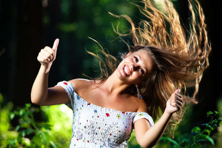 handsign: Young smiling woman with fluttering hair showing success handsign.